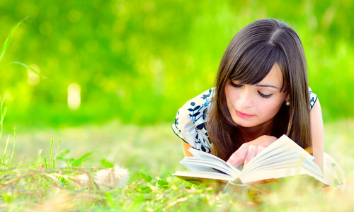cute girl reading while laying on grass